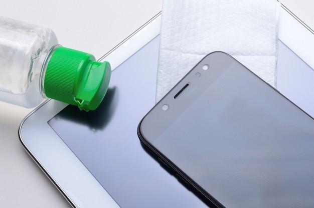 Smartphone e tablet com frasco de gel desinfetante e guardanapo. tratamento antiviral e antibacteriano de dispositivos vestíveis.