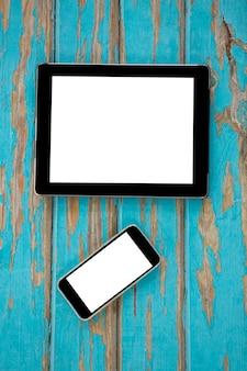 Smartphone e tablet digital na mesa de madeira Foto Premium
