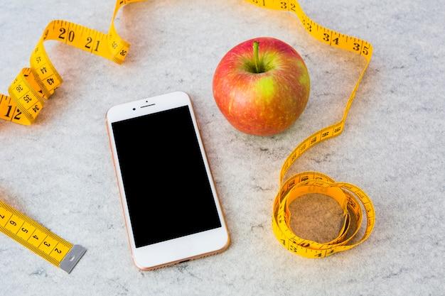 Smartphone e vermelho maçã madura com fita métrica amarela no plano de fundo texturizado cinzento