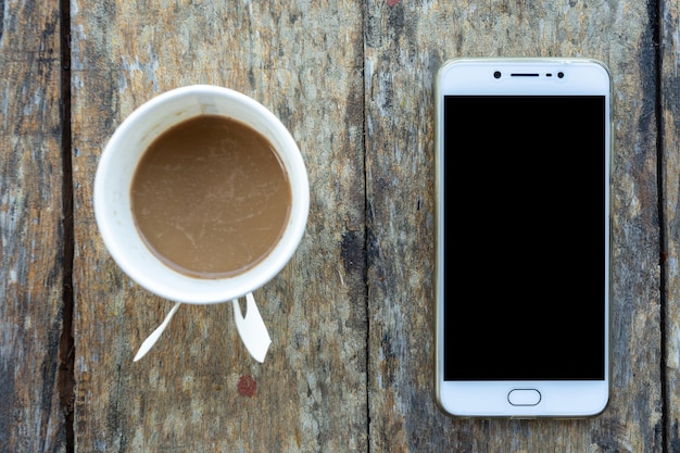 Smartphone e xícara de café de papel na velha mesa de madeira em vista superior. Foto Premium