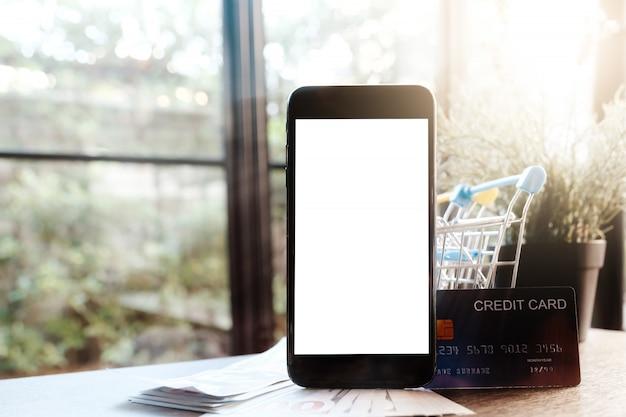 Smartphone em branco com cartão de crédito e dinheiro na mesa
