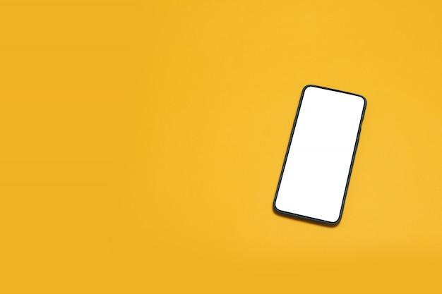 Smartphone em branco no desktop. telefone de vista superior preto sobre fundo amarelo