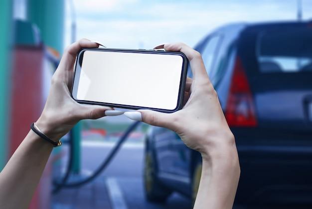 Smartphone em close up de mão no fundo de um posto de gasolina com carro. pagamento de reabastecimento online.