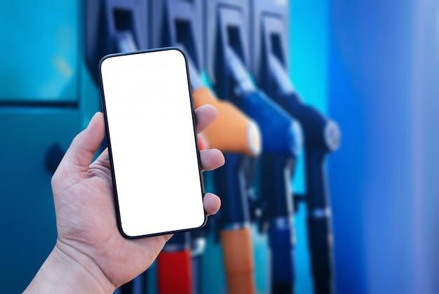 Smartphone em close up de mão no fundo de um posto de gasolina. pagamento de reabastecimento online.
