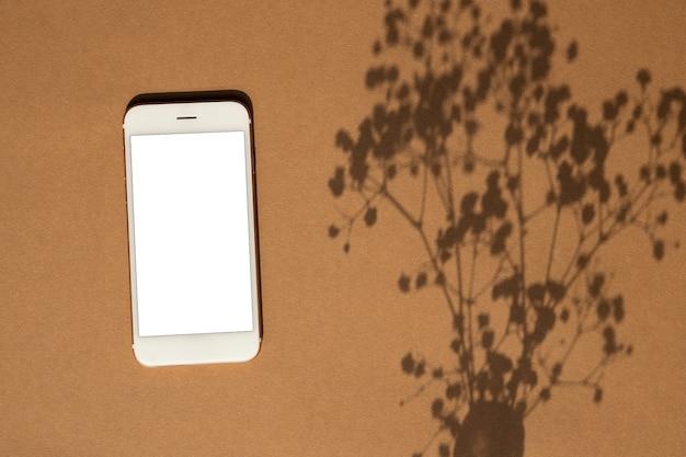 Smartphone em fundo de cor marrom pastel. telefone móvel simule para design de jogos, aplicativos móveis, papéis de parede, sites. vista superior de plantas e sombras