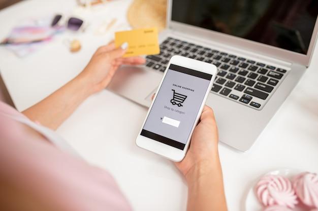Smartphone em mãos de jovem comprador contemporâneo em busca de produtos para adicionar novos à cesta