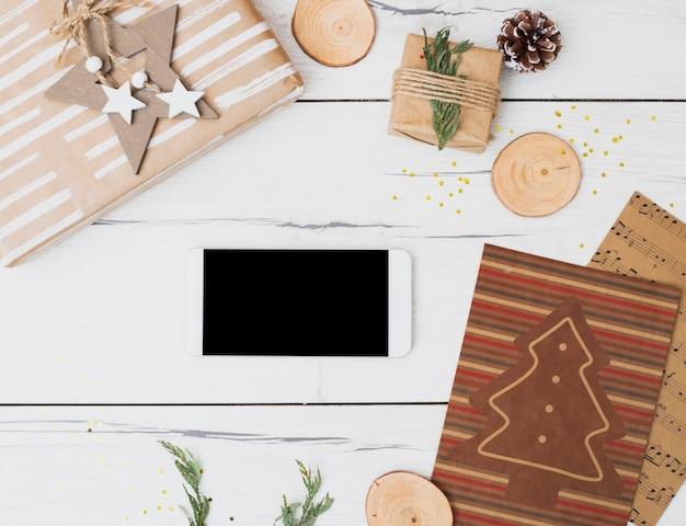 Smartphone entre caixas de presente em envoltórios e decorações de natal