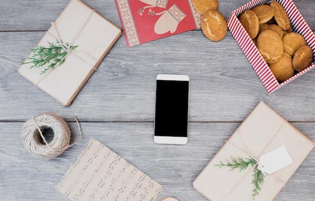 Smartphone entre presentes, biscoitos na caixa, cartões postais e bobina de fio
