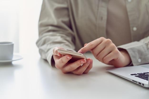 Smartphone feminino irreconhecível que rola o apocalipse no trabalho, conceito de higiene da informação milenar
