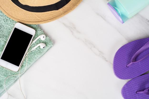 Smartphone, flip-flops, protetor solar e toalha.