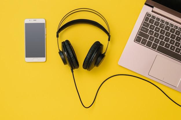 Smartphone, fones de ouvido e um laptop em amarelo