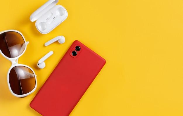 Smartphone, fones de ouvido sem fio e óculos de sol na vista superior do fundo amarelo com o espaço da cópia
