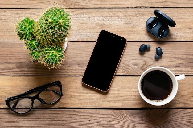 Smartphone, fones de ouvido sem fio, óculos, cacto, cápsula do carregador, xícara de café na madeira