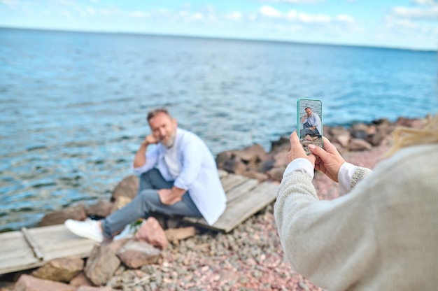 Smartphone, foto. mãos femininas com smartphone fotografando homem sentado, posando na praia em um dia bom