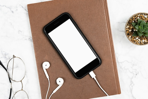 Smartphone isolado tela branca com os fones de ouvido conectados e caderno na mesa