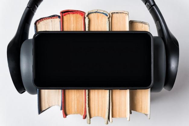 Smartphone, livros e fones de ouvido close-up. vista superior do espaço de cópia de fundo branco