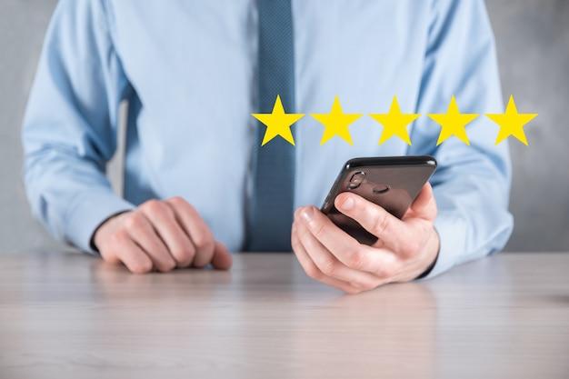 Smartphone mão de homem mostrando uma classificação excelente de cinco estrelas. apontando o símbolo de cinco estrelas para aumentar a classificação da empresa. revisar, aumentar a classificação ou classificação, avaliação e conceito de classificação