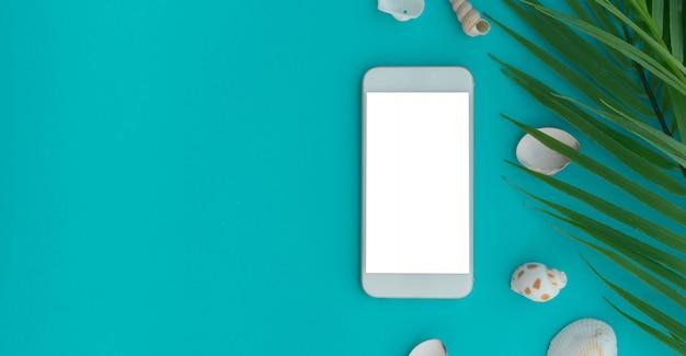 Smartphone maquete branco com concha do mar e folhas no fundo