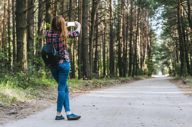 Smartphone maquete nas mãos meninas na floresta, num contexto de árvores. conceito sobre o tema da recreação ao ar livre de viagens.