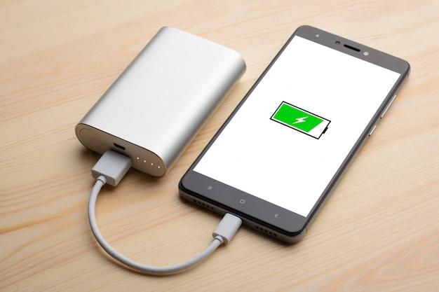 Smartphone moderno coloca na mesa de madeira clara durante o carregamento com banco de potência com carga rápida