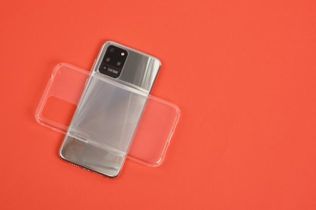 Smartphone moderno com 3 câmeras com corpo de metal e capa de silicone transparente em um fundo vermelho vista de cima cópia espaço câmera hd 100x