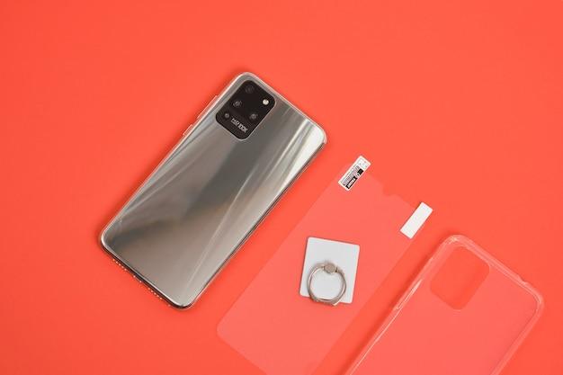Smartphone moderno com 3 câmeras com corpo de metal, vidro protetor, porta-anel e capa de silicone transparente em um fundo vermelho vista superior cópia espaço câmera hd 100x