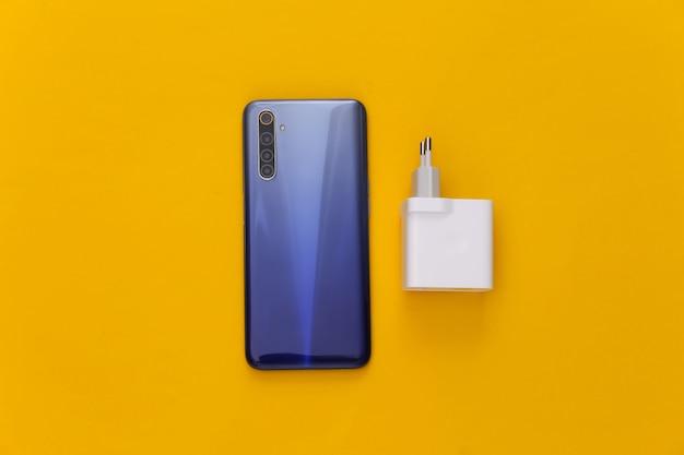Smartphone moderno com carregador amarelo. autonomia de gadgets modernos