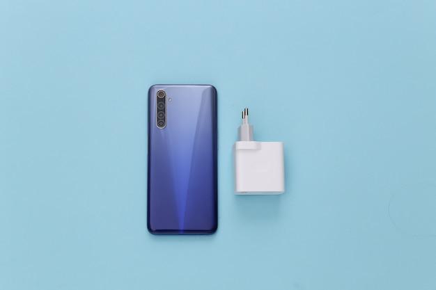 Smartphone moderno com carregador em um pastel azul. autonomia de gadgets modernos