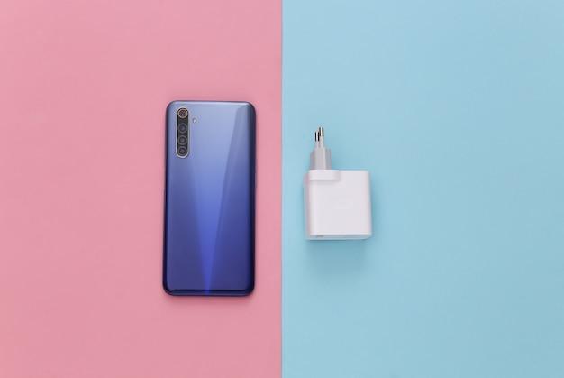 Smartphone moderno com carregador em um tom pastel rosa-azulado. autonomia de gadgets modernos