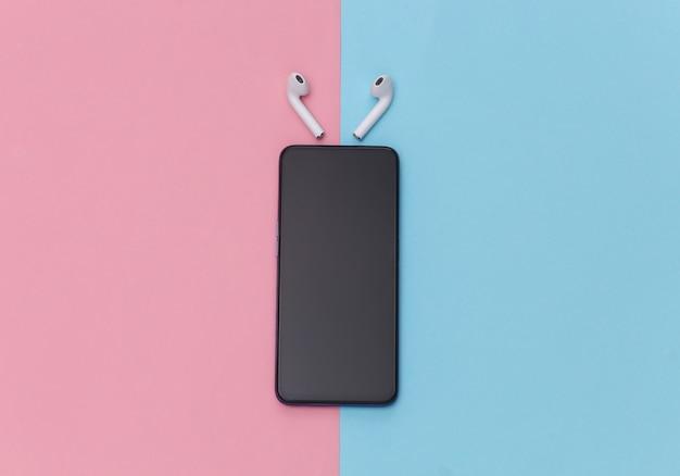 Smartphone moderno com fones de ouvido sem fio em fundo pastel rosa azul.