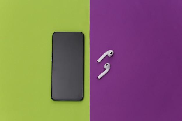 Smartphone moderno com fones de ouvido sem fio em fundo verde roxo.
