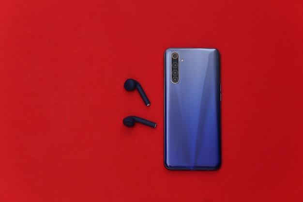 Smartphone moderno com fones de ouvido sem fio em fundo vermelho.