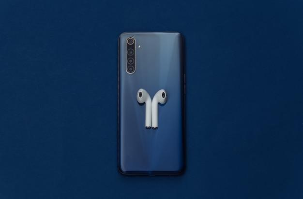Smartphone moderno com fones de ouvido sem fio no fundo azul clássico.