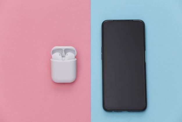Smartphone moderno e fones de ouvido sem fio com capa de carregamento em fundo rosa pastel azul.
