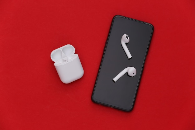 Smartphone moderno e fones de ouvido sem fio com capa de carregamento sobre fundo vermelho.