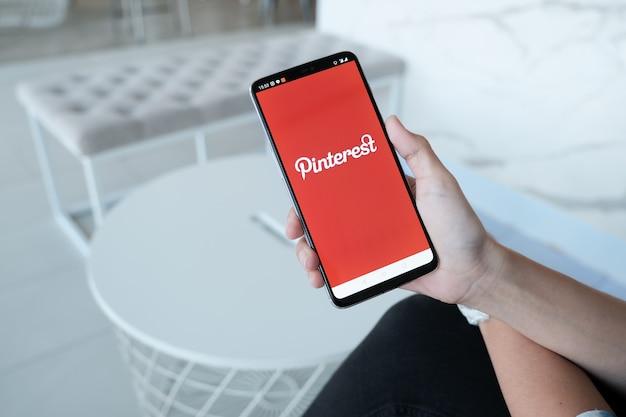 Smartphone mostrando o aplicativo pinterest no celular. foi realizada pela mão do homem na loja de café.