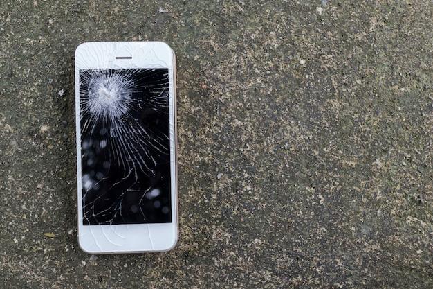 Smartphone móvel cair no chão de cimento com tela de toque mano