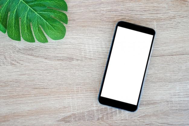Smartphone móvel com tela em branco e monstera deixa na mesa de madeira