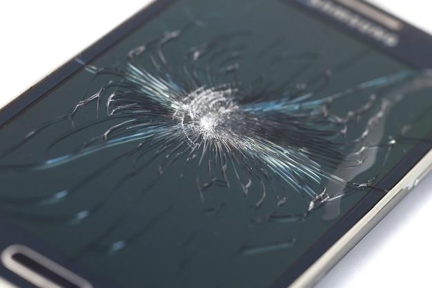 Smartphone móvel com tela quebrada isolada no branco. tela de crack.