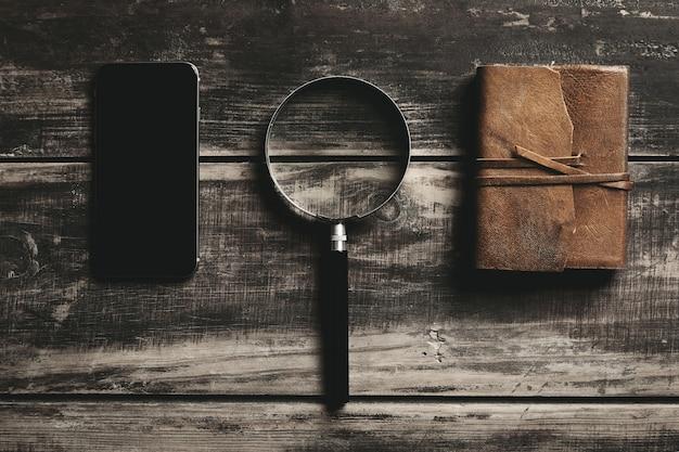 Smartphone móvel, lupa e caderno com capa de couro isolado na mesa de madeira preta da fazenda conceito de jogo de detetive misterioso.