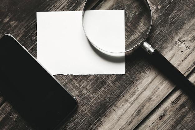 Smartphone móvel, lupa e folha de papel branco isoladas na mesa de madeira de fazenda negra conceito de jogo de detetive misterioso. vista lateral do close up