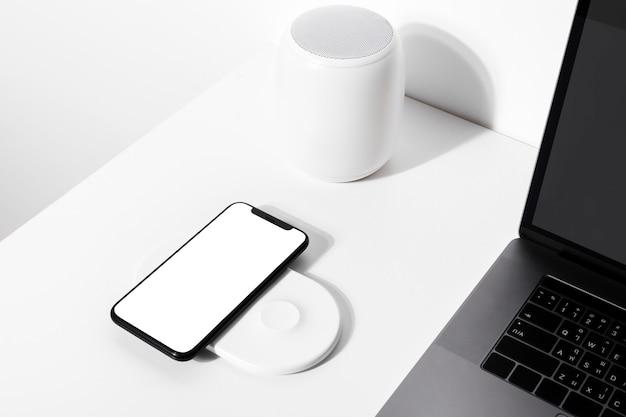 Smartphone na almofada do carregador sem fio branco