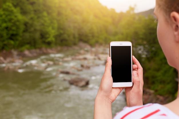 Smartphone na mão de uma mulher, fotógrafo faz foto de natureza bela, tela em branco no dispositivo.