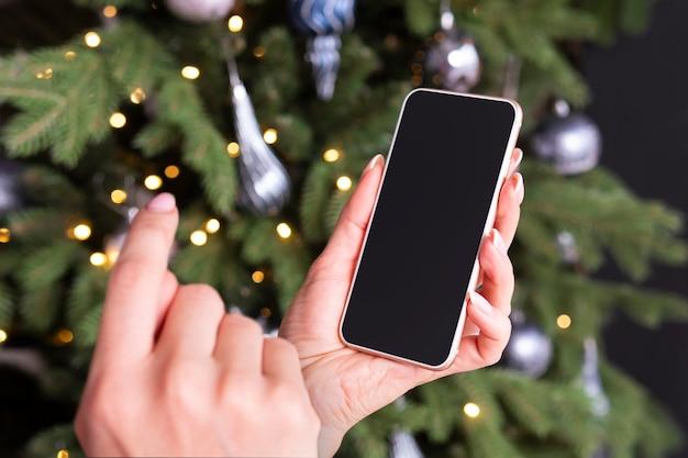 Smartphone na mão de uma mulher no fundo de uma árvore de natal. espaço vazio na tela para design e texto. garota bate na tela com o dedo.