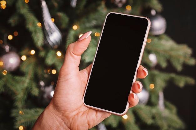 Smartphone na mão de uma mulher no fundo de uma árvore de natal. espaço vazio na tela para design e texto.