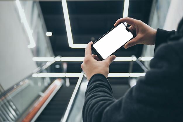 Smartphone na mão do homem na escada rolante