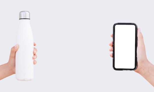 Smartphone na mão e garrafa térmica de aço reutilizável de cor branca