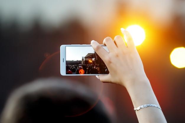 Smartphone na mão grava show de música ao ar livre.