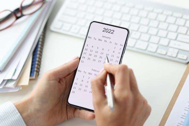 Smartphone na tela com calendário para caneta 2022 em mãos femininas. planejando ideias de negócios para o conceito de 2022