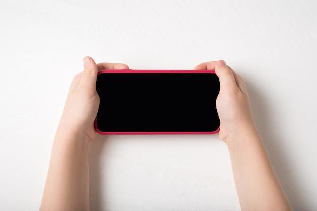 Smartphone nas mãos das crianças, sobre um fundo claro
